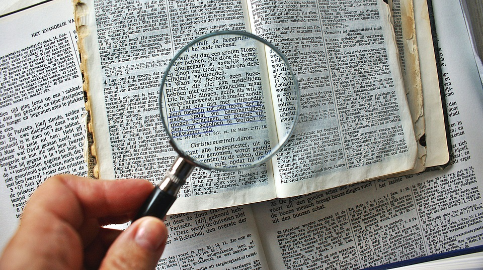 magnifying glass to enlarge book letters bible old