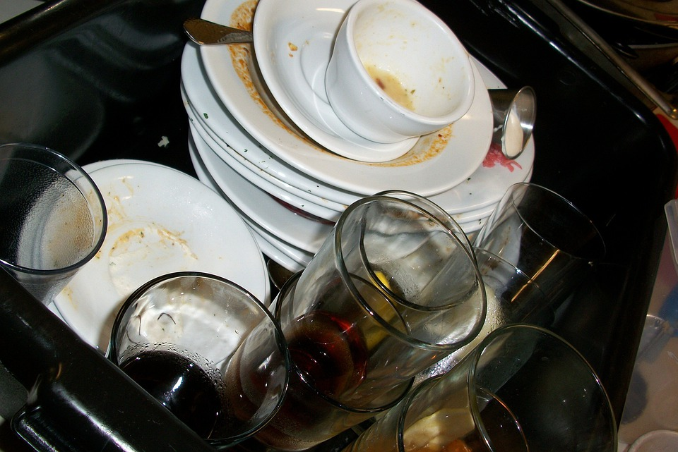 dirty dishes and cups lying in a kitchen sink.