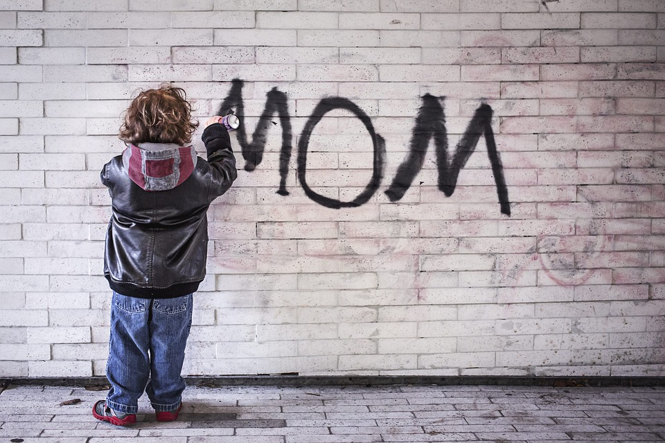 Graffiti image of child spray painting the word MOM