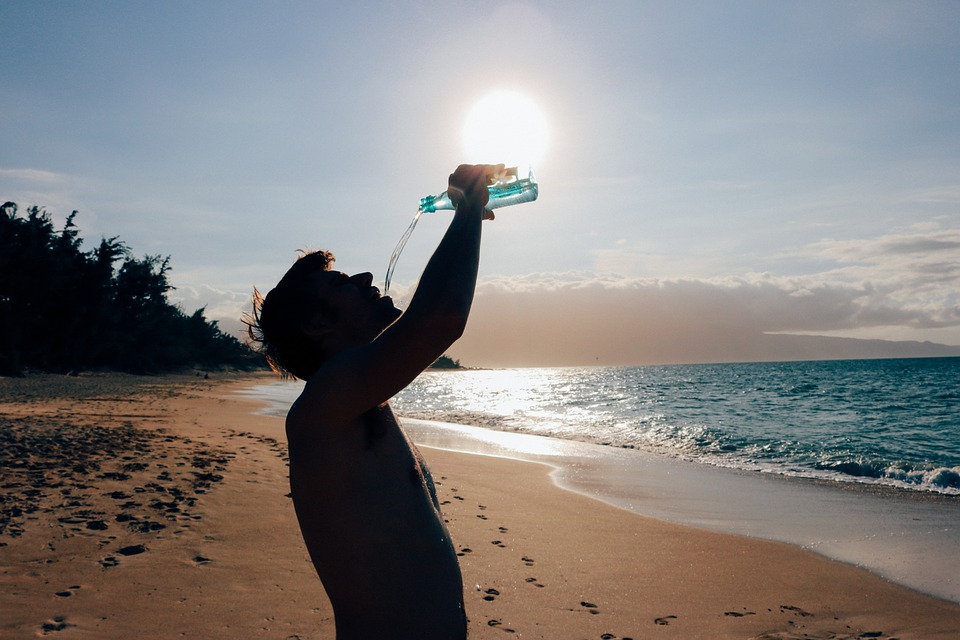 Man Drinking water on a hot day at the beach.