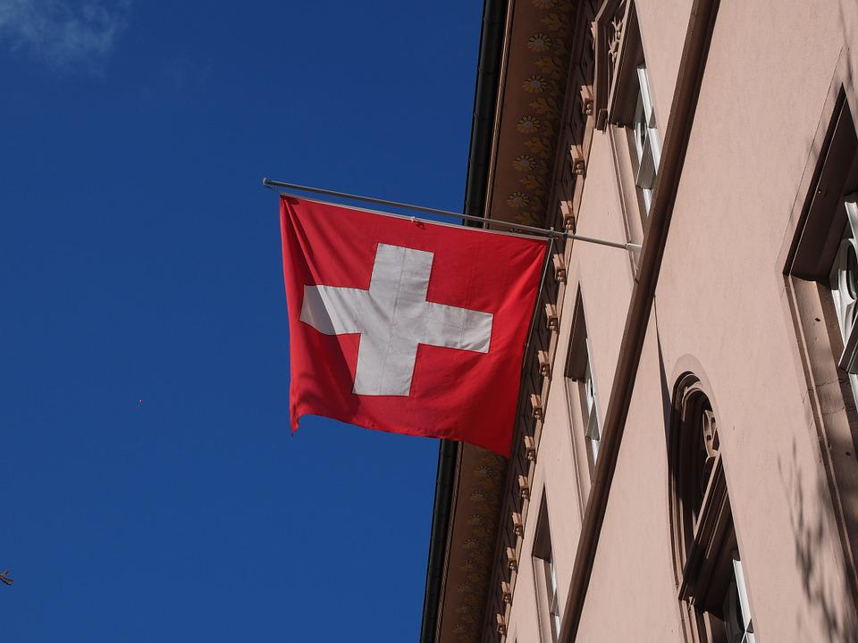 Flag of Switzerland hanging from a building.
