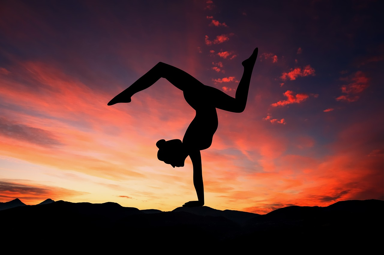 Woman performing yoga pose with mountains and sunset in the background